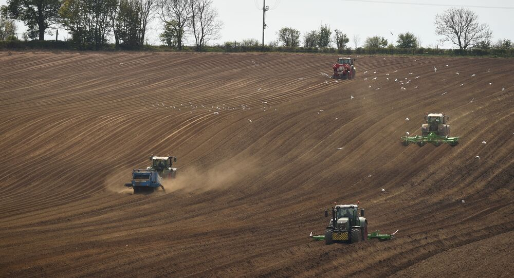 Farmers work in a field with vehicles near Pontefract, northern England, on April 23, 2020