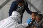 A child is tested by a healthcare worker for the coronavirus at testing center for migrants in Tel Aviv, Israel, Monday, July 6, 2020.