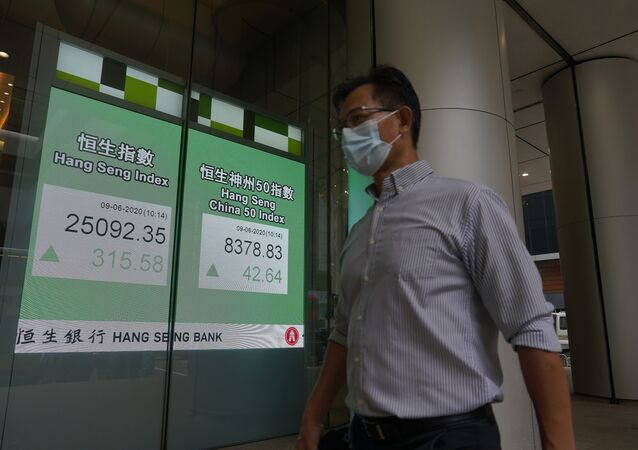 A man wearing a face mask walks past a bank electronic board showing the Hong Kong share index at Hong Kong Stock Exchange Tuesday, June 9, 2020.