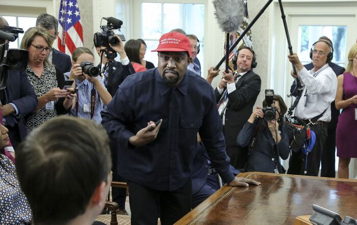 Rapper Kanye West, second left, stands up as he speaks during a meeting with US President Donald Trump in the Oval office of the White House on 11 October 2018 in Washington, DC.