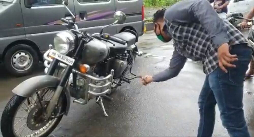 A red sand boa, a non-venomous snake, slithering under the rear seat of a moving Royal Enfield motorbike at Virar (east). The rider was alerted by another biker who saw the moving snake