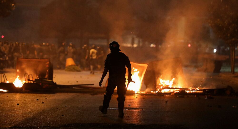 A member of the Lebanese riot police walks near burning fire during a protest against the fall in pound currency and mounting economic hardship, in Beirut, Lebanon June 12, 2020