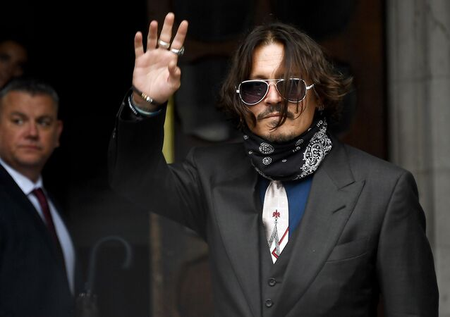 Johnny Depp waves to fans as he arrives at the High Court in London, where he is bringing a libel suit against The Sun newspaper.