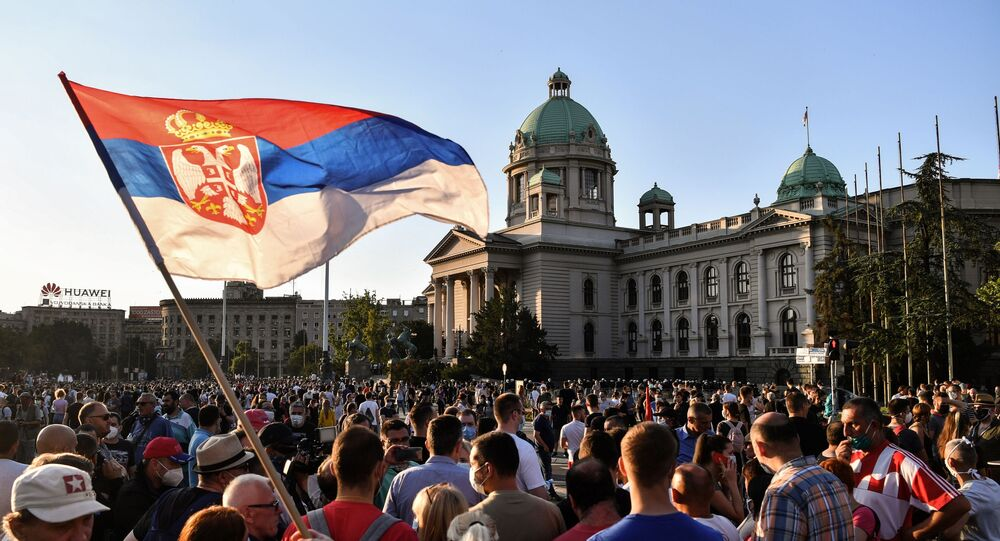 Protesters gather outside Serbia's National Assembly building in Belgrade on July 8, 2020 against a weekend curfew announced to combat a resurgence of COVID-19 infections