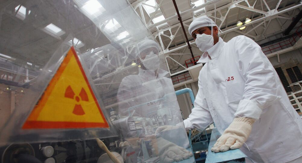 A man in protective gear standing near a hazard symbol