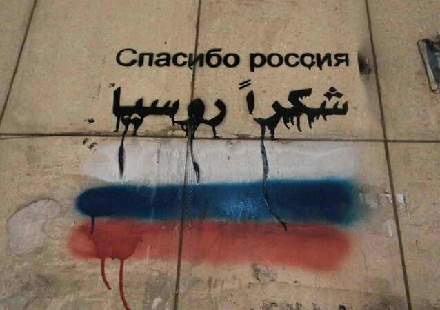 Words Thank you, Russia written on a wall in a Syrian town