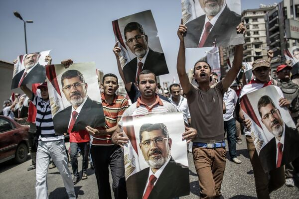 Mohamed Morsi supporters carry posters of the deposed leader as they march in Cairo Monday. - Sputnik International
