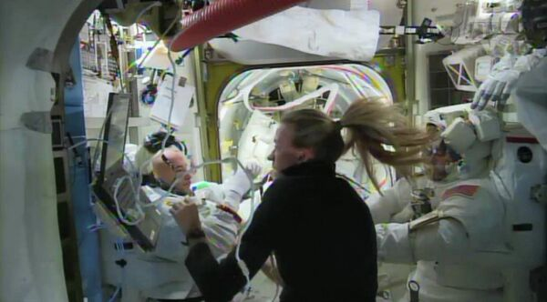 ISS crew member Karen Nyberg helps astronaut Luca Parmitano remove his spacesuit after a leak in his helmet caused a spacewalk to be cut short on July 16. - Sputnik International
