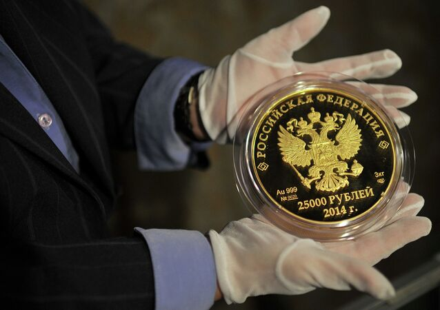 A man presents 25,000 Roubles coin as a part of the Sochi 2014 Coin Program series.