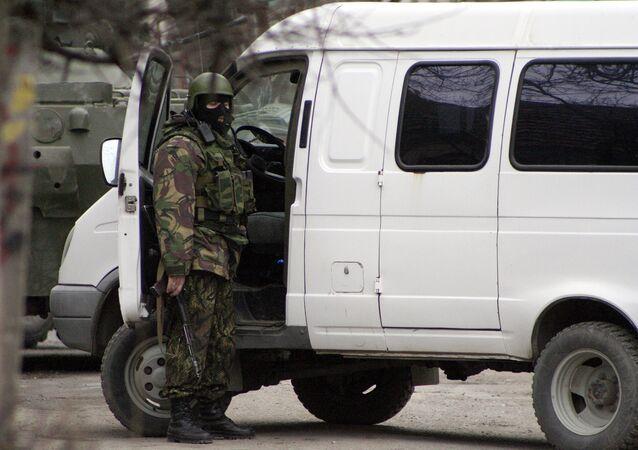 Сотрудник правоохранительных органов у автомобиля во время спецоперации по уничтожению боевиков. Архивное фото