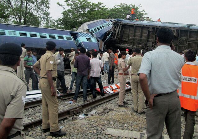 Indian officials and rescuers stand near the wreckage after the Gorakhpur Express passenger train slammed into a parked freight train Chureb, near Basti, Uttar Pradesh state,, India, Monday, May 26, 2014