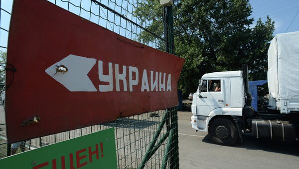 One of the trucks carrying humanitarian aid from Russia to east Ukraine passing a customs point of inspection. Sign on the fence reads: Ukraine. - Sputnik International